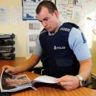 Waikouaiti's Constable Jon-Paul Tremain looks through his file on a series of cat deaths in the...