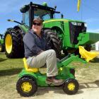 Grant Chalmers, from Southland Farm Machinery, sits astride a toy John Deere front-end loader,...