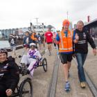 Wanaka's Jup Brown (orange vest) ends his New Zealand marathon run by parading with his father,...
