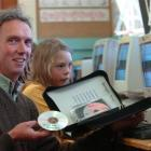 Warrington School principal Nathan Parker and Florence Sorrel (9) compare a single software disk,...
