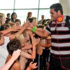 Warriors player Konrad Hurrell high-fives with children from the Fairfield School kapa haka group...