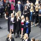 Waving to friends as they take part in the University of Otago graduation parade on Saturday are ...