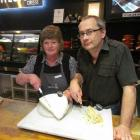 Whitestone Cheese employees Chris Thompson and Martyn Hall carve into a slab  of blue cheese....