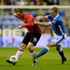 Wigan Athletic's Gary Caldwell (R) challenges Manchester United's Wayne Rooney during their...