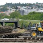 Workmen clear Doug Hall's site at the corner of Anzac Ave and State Highway 88, Dunedin,...