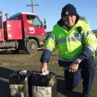 Senior Constable Alex Wynne with two of the three containers of oil left at the intersection of...