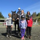 Young disabled rider Tyler Harvey (7), atop horse Billy, is ready to set off for a ride. Joining...