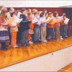 Young voices: Choir master David Burchell puts the children's chorus through its paces during...