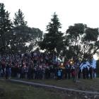 A crowd gathers on the rocky headland and cenotaph flagpole at Lake Hawea for an Anzac Day dawn...