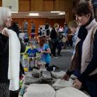 Amanda Caulton (right) checks out hand-knitted scarves displayed by Glynis Cambray at a market...