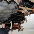 Chris Hope, of Phoenix Services, inspects fire damage in the ceiling of a motel unit at the Tower...