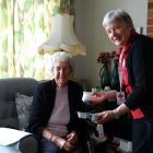 Red Cross Meals on Wheels Mosgiel volunteer Nola King gives Jan Dee her meal. Photo by Joshua...