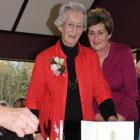 Candles are lit on Hetty Gunn's  100th birthday cake while she laughs with daughter Joan Rowley...