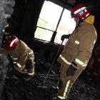 Central-North Otago Fire Risk Management Officer Stuart Ide (left) investigates the cause of a...