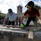 A resident helps a firefighter to set down a crucifix from the damaged San Lorenzo e Flaviano...