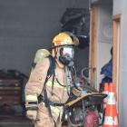 A firefighter attends a blaze at a South Dunedin workshop. Photo by Gregor Richardson.