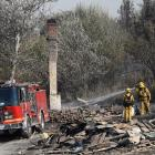 Firefighters hose down a burnt structure at the so-called Blue Cut Fire in San Bernardino County,...