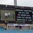 A screen shows umpires and ground staff inspecting the playing surface on the fourth day of the...