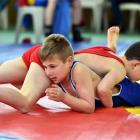 Fletcher Baxter (in red), and Isaac Sinclair, (in blue), both of the Taieri Wrestling Club, take...