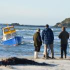Allen Eade (left) watches his boat rolling in the surf. The boat ran aground on the Taieri Mouth...