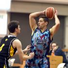 Magic guard Lee Devereaux looks to pass as he is defended by Saints guard James Ross. Photo:...