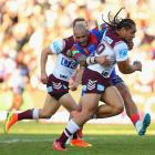 Martin Taupau carries the ball for Manly as he is tackled by Jeremy Smith of Newcastle. Photo:...