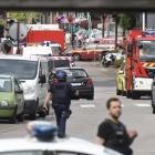 Police and rescue workers stand at the scene after two assailants had taken five people hostage...