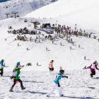 Peak to Peak competitors run to the start of the ski leg at The Remarkables skifield on Saturday....