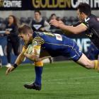Wellington fullback Peter Umaga-Jensen is unable to stop Otago fullback Michael  Barr Stadium...