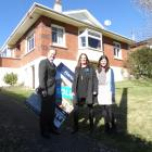 Harcourts Real Estate agents (from left) Mark, Penny and Emma Laughton stand in front of a house ...