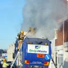 Firefighters dampen down smouldering rubbish on board  a waste disposal truck in Vogel St...