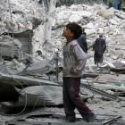 A boy looks at a damaged site after airstrikes on the rebel held Tariq al-Bab neighbourhood of...