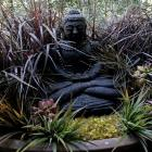 A Buddha that Adam Isaacs bought in Bali sits in a large oval pot surrounded by fake fountain...