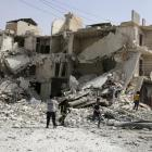 People inspect a damaged site after airstrikes on the rebel held al-Qaterji neighbourhood of...