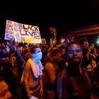 Protesters gather along Mollison Avenue to protest the fatal shooting of an unarmed black man by...