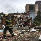 A New York City fire-fighter walks through debris after an explosion ripped through a home in the...