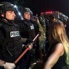 Police officers wearing riot gear block a road during protests after police fatally shot a man in...