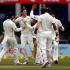 New Zealand's Mitchell Santner celebrates with teammates after taking the wicket of India's...