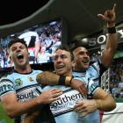 Cronulla's James Maloney celebrates with teammates after scoring against the Cowboys. Photo Getty