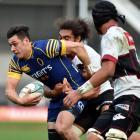 Otago halfback Jonathan Ruru tries to break through the tackle of North Harbour captain Chris Vui...
