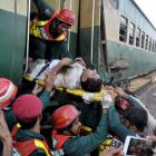 Rescue workers pass a stretcher with an injured passenger out of the wreckage after two trains...