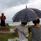 A coast guard stands guard at the coast as Typhoon Malakas approaches in Yilan, Taiwan. Photo:...