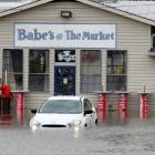 A car sits in flooded waters at a market after Hurricane Matthew passed through in Savannah,...