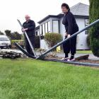 Bill and Pauline Overton inspect the damage to their fence caused when a car ploughed through it....