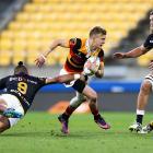 Waikato's Damian McKenzie tries to break through the Wellington defence. Photo: Getty Images