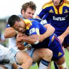 Soakai tries to barge his way through the tackle of the Blues' Jarred Payne during a pre-season...