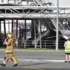 A firefighter walks from the scene of the silo collapse at the Fonterra Edendale plant last month...