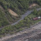 A freight train sits where it came to a halt beside State Highway 1, on the coast north of...