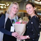 Otago Polytechnic senior lecturer Tania Allan (left) presents a bouquet of flowers to the...