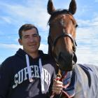 Co-trainer Matthew Pitman holds  First Serve, the stable's big hope for the Pegasus Stakes at...